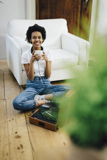 Young woman sitting on grounf listening music from record player, drinking coffee - GIOF03834