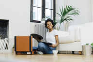 Young woman sitting on grounf listening music from record player - GIOF03837