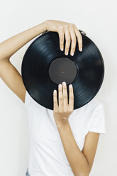 Young woman holding vinyl record in front of her face - GIOF03840