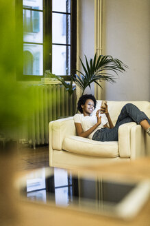 Young woman sitting in armchair, reading smartphone messages - GIOF03846