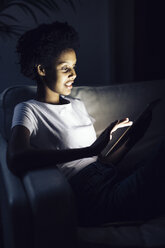 Young woman watching online tv at night, using digital tablet - GIOF03849