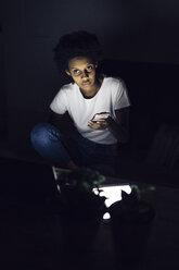 Young woman sitting at home, holding illuminated smartphone at night - GIOF03852