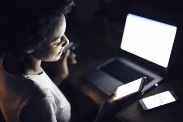 Young woman with credit card, shopping online at night from home - GIOF03855
