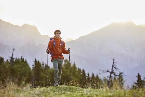 Austria, Tyrol, Mieming Plateau, portrait of hiker on alpine meadow at sunrise - CVF00050