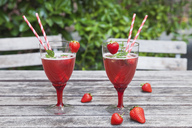 Strawberry lemonade in glasses with drinking straws on garden table - GWF05389