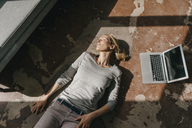 Woman sleeping on the floor next to laptop - KNSF03550