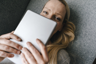 Portrait of smiling woman lying down holding tablet - KNSF03559