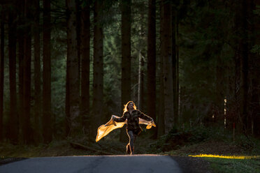 Young woman holding blanket running on country road through forest - WVF00905