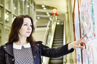 Portrait of young woman looking at city map in underground station - JATF00998