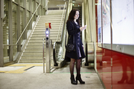 Germany, Cologne, young woman looking at her cell phone in underground station - JATF01007