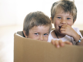 Two happy little children together in a cardboard box - FSF00984