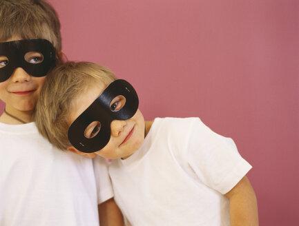 Portrait of two smiling little boys wearing black eye masks - FSF00987