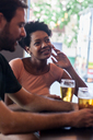 Couple talking and drinking beer in a bar - LFEF00004