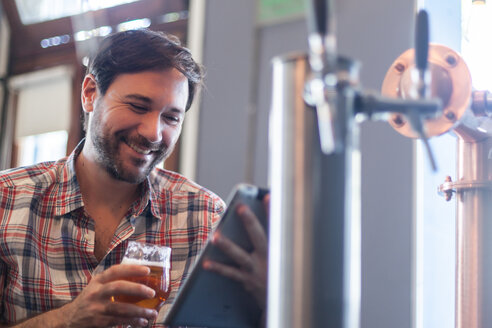 Smiling man with beer glass using tablet in a bar - LFEF00010