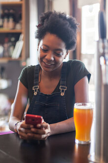 Smiling woman with beer glass using cell phone in a bar - LFEF00013