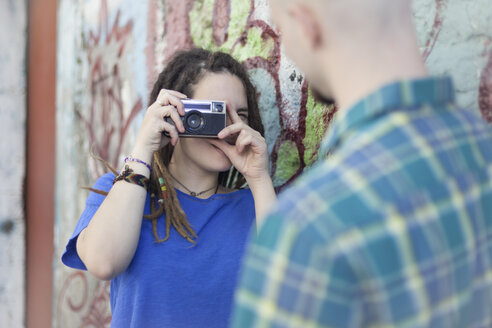 Young woman taking photo of her boyfriend with an analogue camera at graffiti wall - LFEF00016