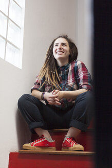 Smiling young woman with dreadlocks sitting on stairs - LFEF00019