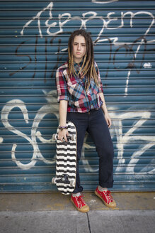Portrait of cool young woman holding skateboard - LFEF00022