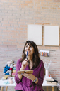 Smiling woman in knitting studio thinking and taking notes - OCAF00032