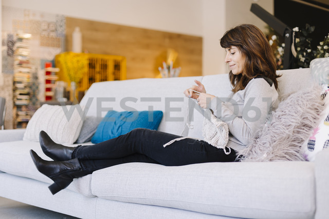 Woman sitting on couch knitting - OCAF00041