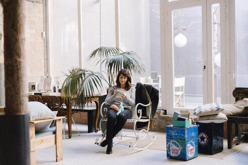 Woman sitting on chair knitting - OCAF00044