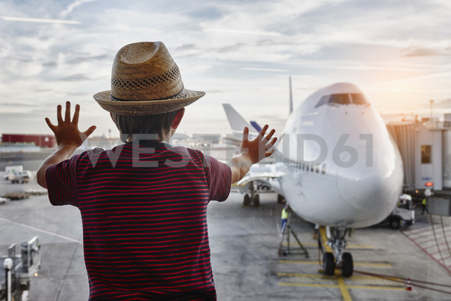 Boy wearing straw hat looking through window to airplane on the apron - RORF01063