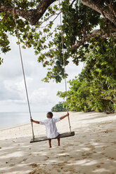 Thailand, Ko Yao Noi, boy on a swing on the beach - RORF01084