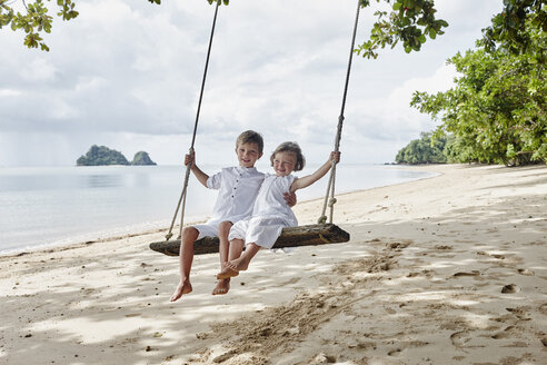 Thailand, Ko Yao Noi, happy boy and little girl on a swing on the beach - RORF01087