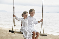 Thailand, Ko Yao Noi, portrait of smiling boy and little girl on a swing on the beach - RORF01090