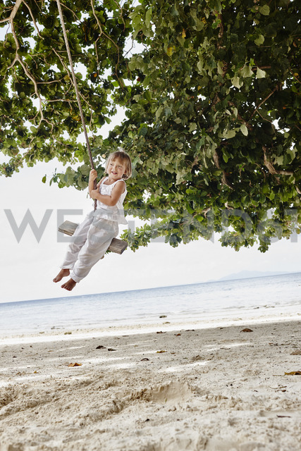 Thailand, Phi Phi Islands, Ko Phi Phi, happy little girl on a rope swing on the beach - RORF01105