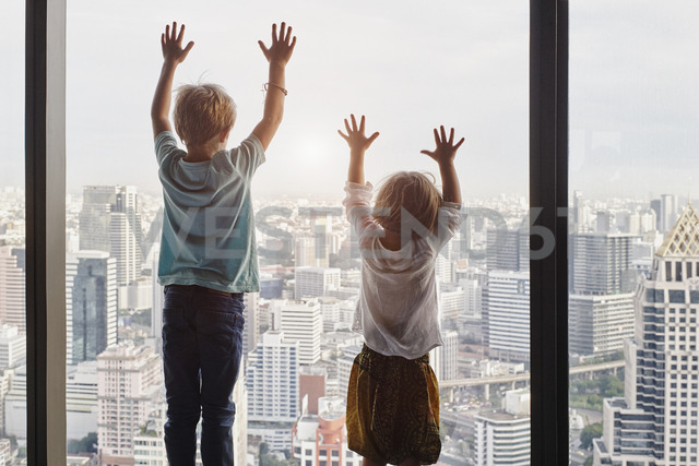 Thailand, Bangkok, boy and little girl looking through window at cityscape - RORF01117