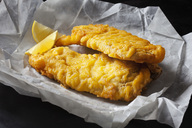 Fried coalfish filet and lemon slices on greaseproof paper - CSF28827