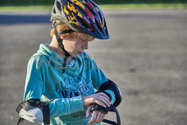 Boy wearing helmet putting on elbow pads - JEDF00298