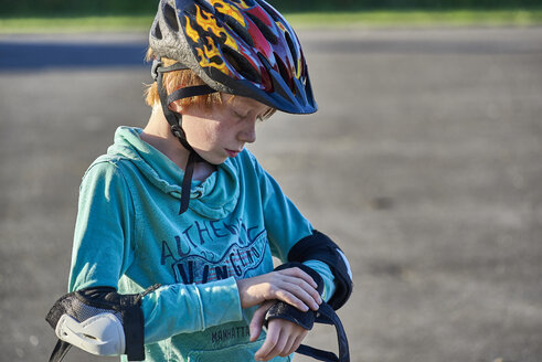 Boy wearing helmet putting on elbow pads - JEDF00298