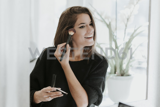 Mirror image of young woman applying Makeup - OCAF00049