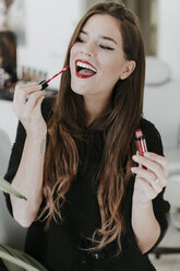 Portrait of happy young woman applying lipstick - OCAF00052