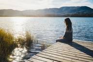 Woman sitting on a wooden platform at a lake at sunset - GEMF01855