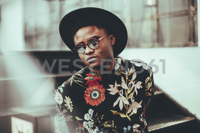 Portrait of fashionable man wearing hat, sunglasses and black t-shirt with floral design - OCAF00057
