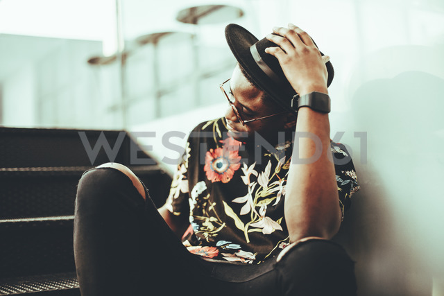 Fashionable man wearing hat, sunglasses and black t-shirt with floral design sitting on stairs - OCAF00060