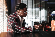 Fashionable young man wearing checkered suit coat looking at cell phone - OCAF00063