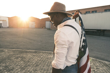 Young man wearing hat and sunglasses holding American flag - OCAF00072