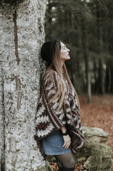 Young woman wearing hat and poncho leaning against tree trunk in autumnal forest - OCAF00075
