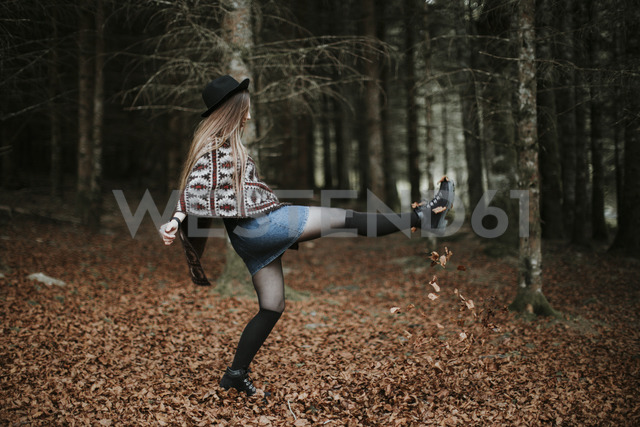 Young woman playing with leaves in autumnal forest - OCAF00078