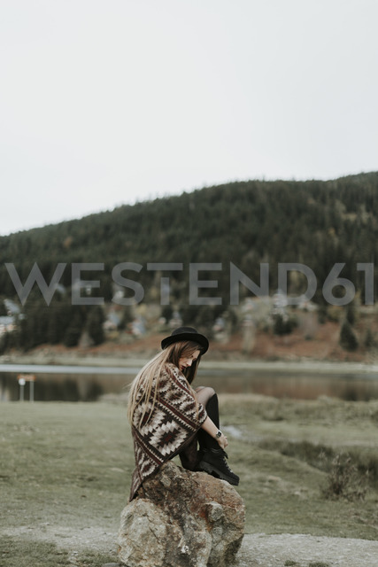 Fashionable young woman wearing hat and poncho sitting on a rock - OCAF00081