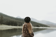 Back view of young woman wearing hat and poncho sitting in front of a lake - OCAF00084