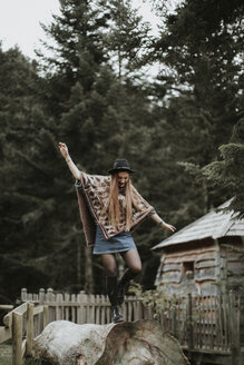 Fashionable young woman wearing hat and poncho balancing on tree trunk - OCAF00087
