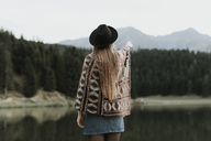 Back view of fashionable young woman wearing hat and poncho standing in front of a lake - OCAF00090