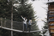 Two young women on a suspension bridge at tree house in forest taking a selfie - OCAF00097