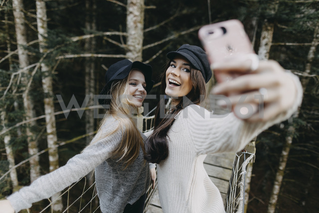 Two happy young women on a suspension bridge taking a selfie - OCAF00100