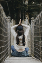 Young woman in yoga pose sitting on a suspension bridge - OCAF00103